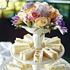 Tea:  Tea sandwiches on a white tier plate with flowers.