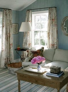 One of the rooms of the extra country house next to the earlier house from Anna Wintour.Nice combo of striped flooring, tongue-in-groove walls painted duck-egg blue, and chinz curtains.A nice simple feel.