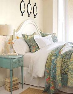 Cottage Bedroom: curvy white wood bed, layers of white bedding with quilt of soft blues & greens, antique-blue bedside table, and a glass lamp ... so inviting