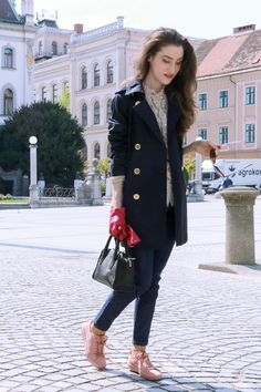 Fashion blogger Veronika Lipar of Brunette From Wall Street sharing her spring chic business attire in pale pink sneakers and dark blue jeans and blue trench coat