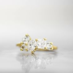 A unique combination of diamond shapes in a clustered prong setting, this engagement ring wraps around the top of the finger with elegance and sophistication. This design features an oval, two cushion, and two round white diamonds perfectly set together to create an asymmetrical yet whimsical look. The signature Wanderlust textured band creates a subtle and organic feel that will wear perfectly over time.