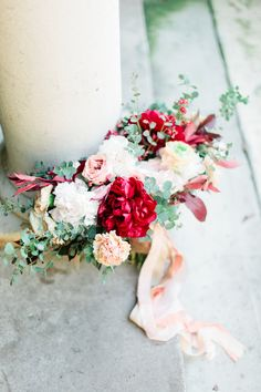 Vibrant red and blush wedding bouquet with pink ribbon
