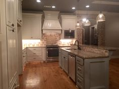 Kitchen with pine floors, large island, granite, and custom tile detail.