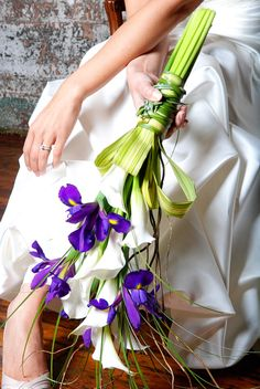 Modern style bouquet of blue iris, white mini calla lilies, flax leafs and bear grass, handle is wrapped with flax leafs and embellished with rhinestone accents.