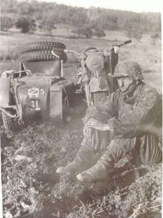 A soldier resting next to his motorcycle while performing reconnaissance duties.