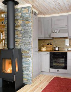 LUN PEIS: Den nye peisovnen gir godt med varme og er et stemningsskapende innslag på kjøkkenet. Den røde ryen hadde hytteeierne fra før.