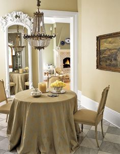 neutral dining room with small table and chandelier