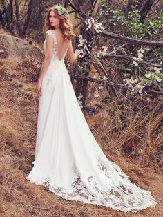 Maggie Sottero - ESTELLE, This romantic Orlando Satin wedding dress features lace appliqués accented in beads and Swarovski crystals along the bodice, illusion V over sweetheart neckline, cap-sleeves, and open V-back. A cutout train comprised of illusion lace appliqués completes the unique glamour of this look. Finished with zipper closure.