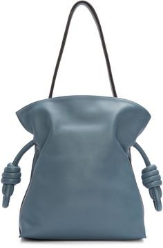 Unstructured nappa leather bag in 'stone' blue. Single adjustable shoulder strap. Drawstring closure at throat with knotted ends. Anagram logo embossed at bag face. Inset magnetic closure at bag throat. Zip pocket and press-stud fastened patch pocket at interior. Fully lined. Silver-tone hardware. Tonal stitching. Approx. 10