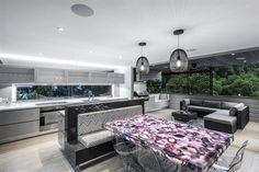 Open plan living area with backlit geode (quartz) dining table - Interior Design Mag