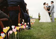 Paper hearts on wooden dowels, made by the couple, lining the aisle for the ceremony 40 Personal DIY Details From Real Weddings