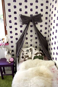 Love the bow hanging off crib with purple side table. And check out those pillows! In LOVE with this look.