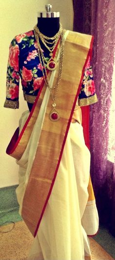 Traditional white saree with a bold red and gold border, accompanied by an elegant floral blouse.