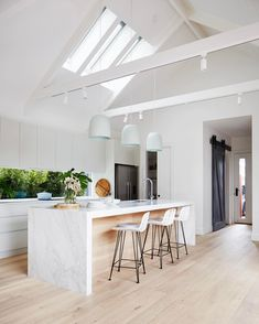 timber flooring Kitchen with pitched cathedral ceiling and exposed beams. A trio of large pendant lights hang over the white marble kitchen island. The glass splashback welcomes the outdoors in, and white cabinetry pairs with pale blonde timber flooring. Home Decor Kitchen, New Kitchen, Home Kitchens, Country Kitchen, Modern Kitchens, Vintage Kitchen, Nordic Kitchen, Decorating Kitchen, Modern Kitchen Design