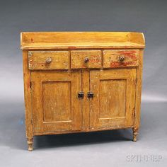 Country Yellow-painted Pine Cupboard, 19th century, the rectangular top with gallery over a case of three short drawers and two hinged, paneled doors, raised on turned feet, the yellow over an older red paint, ht. 47, wd. 49, dp. 17 1/2 in.