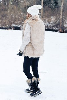 fall / winter - street style - street chic style - winter outfits - casual outfits - white pom pom beanie + beige oversized sweater + beige fur vest + black skinny jeans + snow boots
