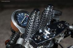 """イタリア最古のオートバイメーカー「MOTO GUZZI(モトグッツィ)」といえば、車両自体が既に完成されたフォルムであるという考えが主流であり、ハードにカスタムを施すことは珍しい。 しかし今回紹介する車両は、原型をとどめないほどにビルドアップされた珠玉のカスタム・モトグッツィだ。  極限までストリップ  エンジンとフレーム以外は、ほとんどのパーツが変更されるか取り外されており、原型をとどめていない「1000 SP」。こちらの車両を製作したのは、イタリアのカスタムショップ「FIFTY FIVE GARAGE」だ。   ヘッドライトはサイドに移植されており、ハンドルはセパレートハンドルをチョイス。バーエンドミラーにすることで、ハンドル周りの""""もっさり""""感を払拭している。   フロントはスプリンガーフォークへと変更され、中央に革巻きされたスピードメーターが鎮座する。   タンクやシートカウルはアルミで製作され、上から薄めのペイントをした後にエイジング加工が施されている。   横からのカットでは、もはや往年の英国レーサーレプリカ(カフェレーサー)そのもの。…"""