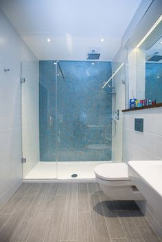 Wood effect floor tiles, white wall tiles and aqua blue mosaics in this en suite…