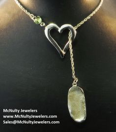 This beautiful sterling silver necklace was created to commemorate the newest addition to a family and features the child's fingerprint and birthstone. McNulty Jewelers original design