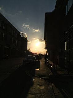 Sun setting in built up town with cars