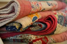 i love this stack of old quilts
