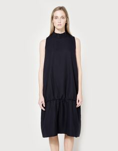 Contemporary shift dress from NEED in Navy. Wide mock neckline. Concealed back zip closure. On-seam side pockets. Drop waist with shirred detail at seam. Unlined. Made in USA with imported materials.    • Amunzen  • 100% polyester  • Dry clean  • Made in