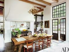 Architect Bobby McAlpine and interior designer Ray Booth collaborate on a Cape Dutch–inspired home in Baton Rouge, Louisiana. A 17th-century portrait overlooks the kitchen table, which is surrounded with antique French chairs; the range is by La Cornue, and the custom-made doors feature hardware by the Nanz Co. | archdigest.com