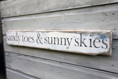 Strikingly beautiful sign made from a piece of English driftwood.  Adorned with the words:    sandy toes & sunny skies    Elegant slate grey