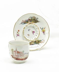 Trembleuse Cup and Saucer with Landscape Decor.   Meissen. Circa 1750/60.     Porcelain, enriched with colours. Gold edge. Finely wrought depictions of river landscapes with figural staffage and scattered flowers. Height 7cm/ + 13,5cm.   Cup probably slightly later.   Crossed swords mark. Cup with the press number 17, saucer with 63.