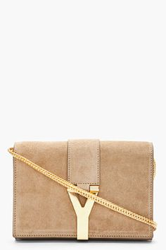 "SAINT LAURENT //   Beige suede logo shoulder bag    31069F070002    Small structured suede shoulder bag in beige. Gold-tone hardware. Foldover flap at main compartment with logo piece concealing magnetized press-stud closure. Removable snake chain shoulder strap. Two compartments at interior with logo stamp and patch pocket. Fully lined. Tonal stitching. Approx. 6,5"" length, 2"" width, 5"" height. 100% leather. Made in Italy.    $1195.00 USD"