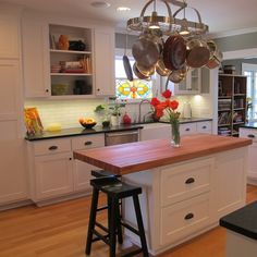 Take advantage of all of the space in your kitchen by installing a hanging rack for pots and pans above your kitchen island. Next step: figure out what you're going to do with all of that extra cabinet space!