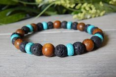 Turquoise mens bracelet is made with Volcano Rock, 9mm Natural Wood and Turquoise Howlite Rondelles. Earthy and strong. Popular mens beaded bracelets.