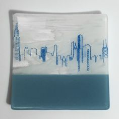 This platter features my linear Chicago Skyline drawing screen printed in light blue enamel onto wispy white-clear with opaque powder blue glass, then fused in a kiln to about 1400 degrees. After that