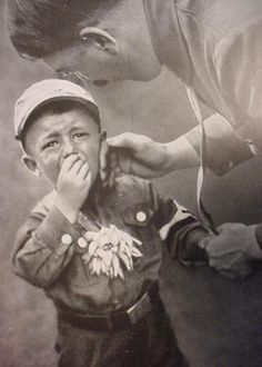Little boy in SA outfit appears a bit overwhelmed by his Fuhrer's attentions.