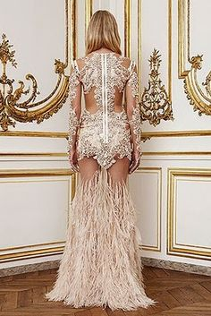 Givenchy, Fall/Winter 2010. Skeleton-like embroidered ivory lace and feather gown. Dress is long sleeved and floor length.