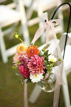 Fresh flowers in jars hanging from shepherds hooks beside aisle chairs.