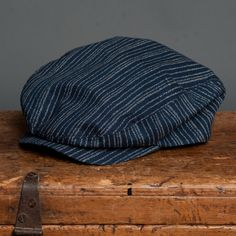18 Waits | Billy Cap | Indigo Stripe $115  Billy Caps are hand-made in Montreal. Based on a vintage pattern and updated by 18 Waits. Wool is sourced from Woolrich Woolen Mills in Pennsylvania. This Fall/Winter we are offering three variations: charcoal herringbone, light grey herringbone, and brown plaid. Trimmed with a super-soft leather sweatband.