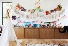 Kid's playroom with built-in storage, Confetti System garland, handmade art, and tepee.