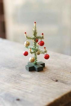 """Miniature Christmas tree complete with ornaments and old fashion candles. 4-1/2"""" tall."""