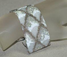 Je gesehen ein Drachenschuppen im Winter? Dies ist, gerade wie ich sich vorstellen, dass sie mit Eiskristallen und flauschigen Schnee bedeckt und in der kalten Wintersonne glitzernden aussehen würde.    Erstellt von Perlen aus Matte Kohlenstoff-Stahl, grau meliert, Schneewittchen, eisigen Kristall und Matte transparent klar Perlen, diese schmaler Version von meinem Drachenschuppen-Design ist immer noch eine Wucht. Verbinden Sie es mit einem einfachen weißen T-shirt und Jeans, Ihre Lieblings…