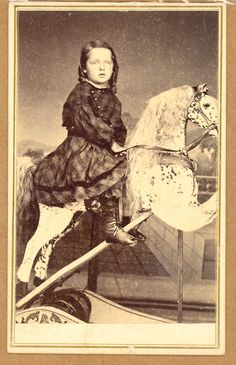 Boy in tartan dress and trousers/pantaloons. ca. 1860's. Posed on a rocking horse.