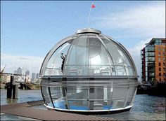 Marcin Panpuch glass sphere house- a spherical, transparent houseboat designed to solve London's housing shortage. The sphere would be divided into three floors, each built around a central core holding the stairs, kitchen, and bathroom. Inhabitants would use the lower floor as a bedroom, the upper floor as a living space, and the bottom floor (below the surface of the river) for storage, water tanks, heating, and computers. Retractable screens would be used for privacy
