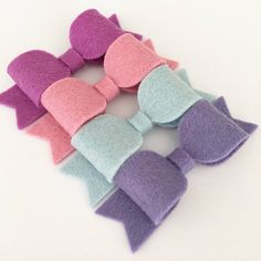 ABOUT ............ A pretty set of 4 pink, blue and purple hair bows. You will receive all 4 bows. This pretty set of small bows is perfect for both children and adults alike. The bows are made using 100% wool felt. Each bow measures approx. 6cm long. The bows are attached to a