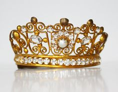This is a old brass/gilted crown for a santos. This crown is from France and is early 1800s. With clear stones faceted stones and pearls. This is an extemely rare piece as I have never had one with pearls.    This crown is simply stunning dating back to the 1800s and displaying the most gorgeous stones set in the gilt ormolu. It is French in origin and was once used on a statue or santos in a chapel or private shrine. A great crown/tiara to add to your collection or start one with. The s...