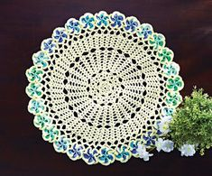 Mary Maxim - Floral motifs are joined around the center creating this stunning table topper. Shown in Linen/Cool Waters or choose any 2 Mary Maxim Fresh colors.