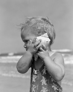 """poboh: """" Blond Toddler Girl Listening To Ocean In A Seashell Wearing Teddy Bear Bathing Suit, 1950's """""""