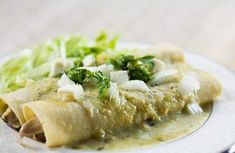 Chicken enchiladas with a salsa verde sauce made with tomatillos, serrano chile peppers, and sour cream. Served with chopped onion, Mexican cheese, and cilantro.