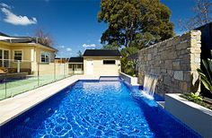 Pool and spa with blue mosaic tiles and waterfall coming out of the stone wall. c.