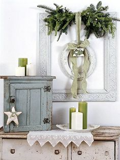 Layer pieces to create a seasonal display. Hang a large empty frame on the wall, then use a wide ribbon to suspend a smaller one in the center. Tuck a swag of greenery under the ribbon along the edge of the top frame, and tie an ornament to the bow that holds the small frame