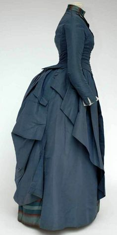 Day dress, ca. 1885-90. Blue silk with woven stripes of red, blue, and light blue, blue cord, and glass beads. Boned bodice lined in beige cotton, asymmetrically-draped skirt in brown cotton. Hem reinforced with black linen. Mode Museum, Antwerp